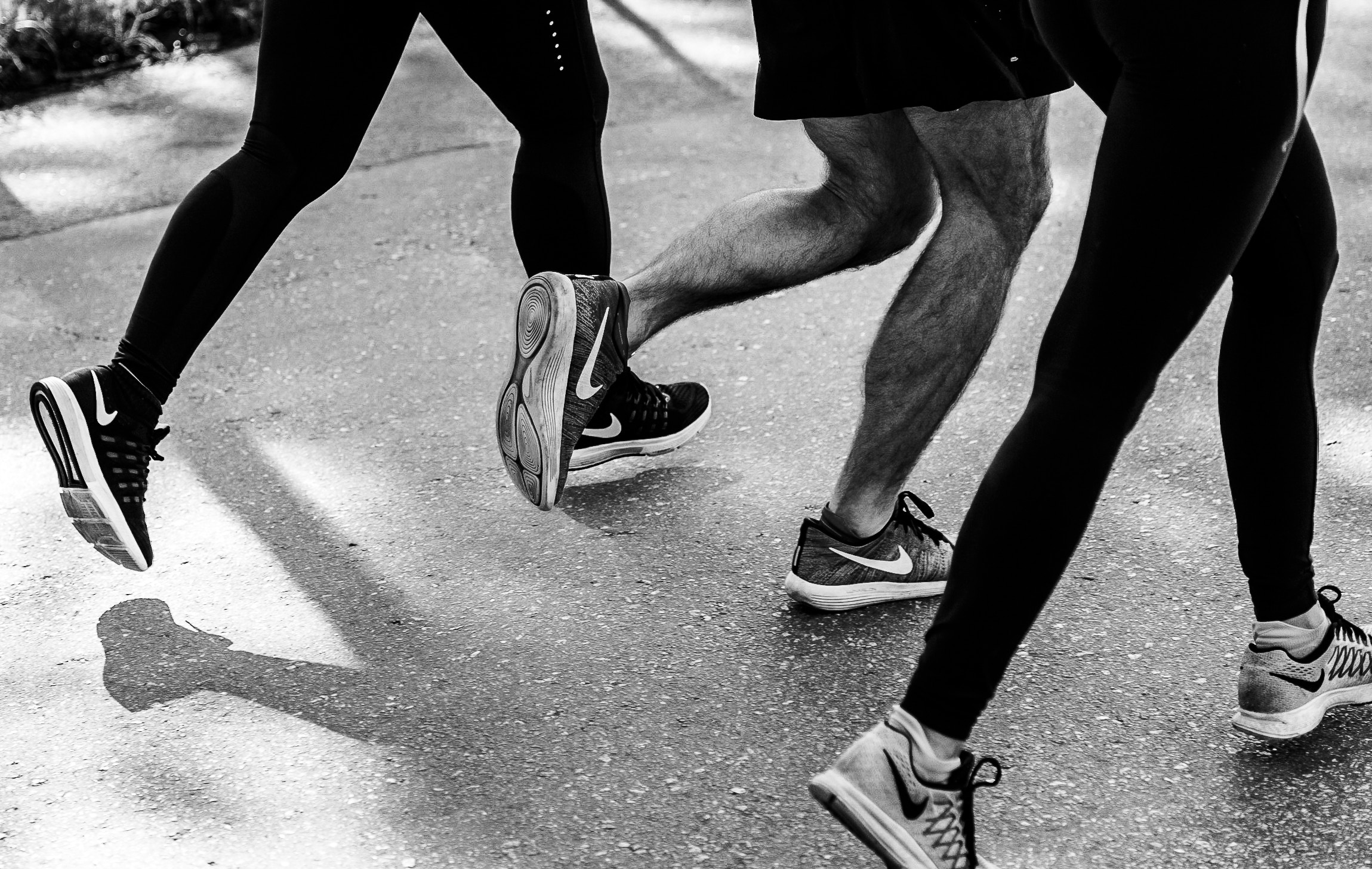 three people running in black and white photo